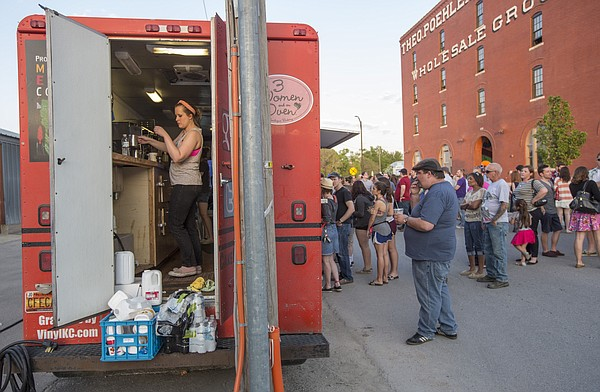 Sara Danner, of Kansas City, Mo., works in the back of the Coffee Cake KC food truck while customers line up outside during the second annual Lawrence Food Truck Festival Saturday evening in east Lawrence.