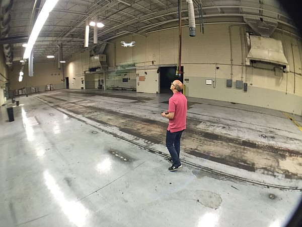 Journal-World photographer Nick Krug practices flying a small drone in the vacant room that once held the Journal-World printing press.
