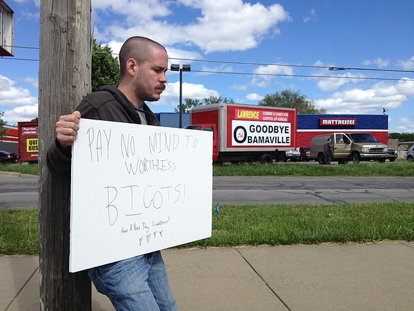 Adam Dorsson, of Lawrence, holds a sign in front of Payless Furniture's goodbye signage, Monday, May 11, 2015.