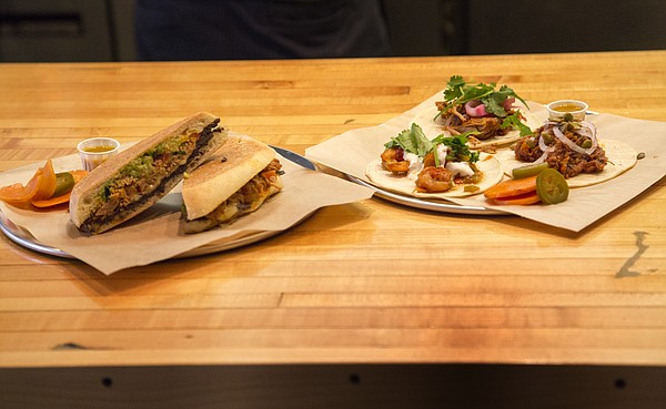 From left, a torta with roasted pork and a variety of tacos are pictured at Taco Zone at 13 E. Eighth St.