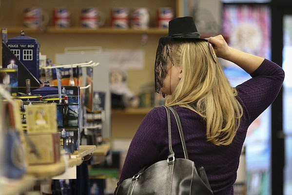 "Brits shopper Beth Smith, of Topeka, tries on a veiled hat in the fashion of the popular British drama ""Downton Abbey"" on Thursday, May 14, 2015, at the downtown store."