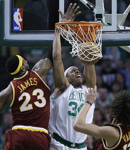 Boston Celtics forward Paul Pierce, center, dunks as Cleveland Cavaliers forward LeBron James, left, and center Anderson Varejao of Brazil, right, watch during the second half of Game 4 in a second-round NBA basketball playoff series, Sunday, May 9, 2010, in Boston. The Celtics won 97-87, tying the series at 2-2. (AP Photo/Charles Krupa)