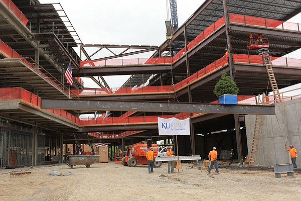 The final beam of Capitol Federal Hall, the new Kansas University School of Business building under construction on Naismith Drive, is lifted into place on Wednesday, May 13, 2015. As part of a topping-out tradition, an American flag and a tree are placed on the beam, which signifies that the structure has reached its maximum height and symbolizes a reverence for the na
