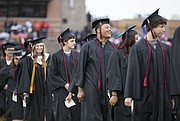 Diondre Jones-Sanders flashes a smile as he and his classmates make their way toward their seats for the 2015 Commencement on Tuesday, May 19 at Lawrence High School.