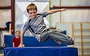 Eleven-year-old Christian Bandel uses one arm to spring over a vault during a parkour class held at Lawrence Gymnastics Academy, 4930 Legends Dr. on Sunday, May 17, 2015.