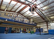 Fourteen-year-old William Gallagher leaps high in the air off a balance beam during a parkour class held at Lawrence Gymnastics Academy, 4930 Legends Dr. on Sunday, May 17, 2015.