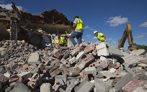 Workers with King's Construction separate scraps of metal from brick and concrete during the demolition process of the former Ramada Inn building located at 2222 West 6th Street, on Tuesday, May 26, 2015. The property, which is owned by Lawrence-based Williams Management, is expected to be redeveloped.