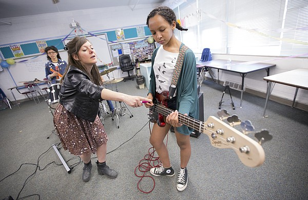 Kelly Nightengale, left, coaches bassist Amaya Harris during a practice session with the Extraterrestrigirlz at the Girls Rock Lawrence camp, Tuesday, June 2, 2015 at Saint John's Catholic School.