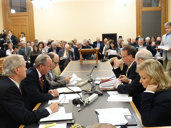 House and Senate tax negotiators meet in a packed committee room to discuss how to raise more than $400 million in new taxes next year.