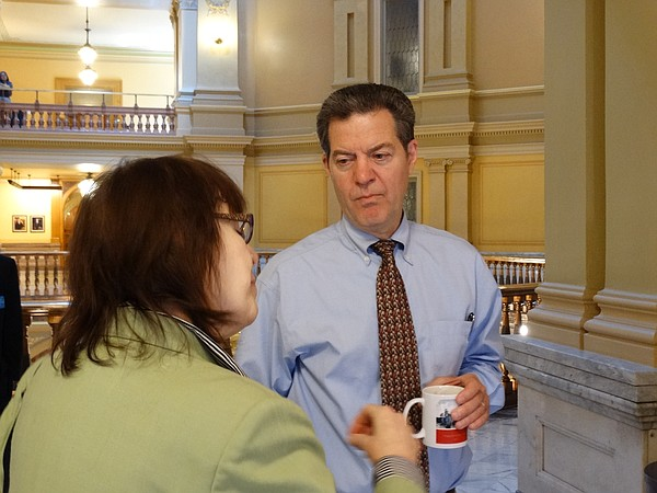 Gov. Sam Brownback talks with Rep. Jan Pauls, R-Hutchinson, outside the House chamber. Afterwards, he told reporters he is urging lawmakers to pass the Senate's tax plan, along with a trailer bill to clean up provisions that many lawmakers find objectionable.