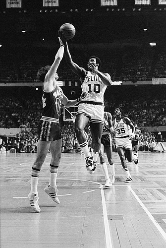 Boston Celtics' Jo Jo White lays up a shot over Golden State Warriors' Rick Barry, in their National Basketball Association game at the Boston Garden, Feb. 29, 1976. Boston won the game 119 to 101. (AP Photo/J. Walter Green)