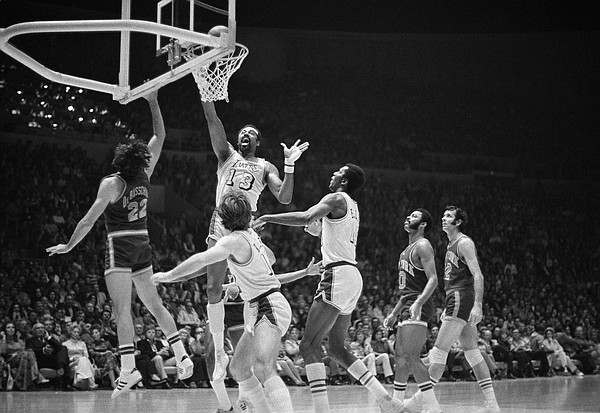 Wilt Chamberlain, named the most valuable player in the NBA playoffs, goes up to tap in a basket for the Los Angeles Lakers against the New York Knicks, May 8, 1972 in the Forum. At left is Dave DeBusschere of the Knicks and in foreground are Pat Riley and Leroy Ellis, right, of the Lakers. Los Angeles won, 114-100, to capture the first championship since the team moved to Los Angeles from Minneapolis 12 years ago. (AP Photo/David Smith)