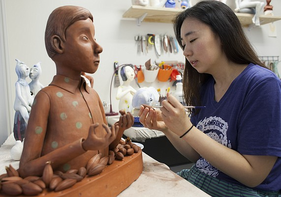 Lawrence artist-in-residence Gunyoung Kim works on her artwork Thursday at the Lawrence Arts Center. Kim will have her work on exhibit starting June 26 at the Lawrence Arts Center.