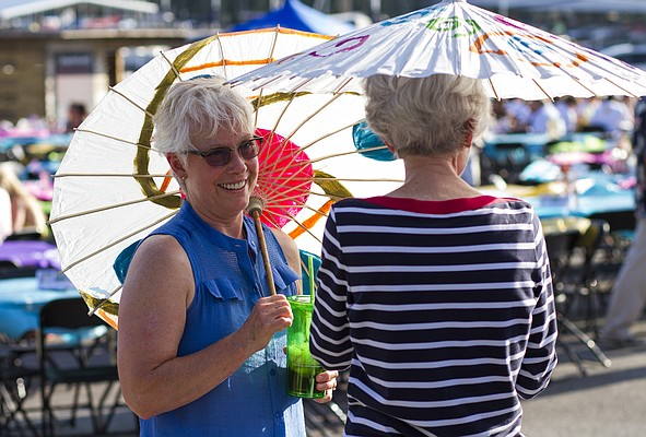 Becky Browning, left, of Baldwin, and Virginia Corran, of Lawrence, use umbrellas to shield themselves from the hot sun as they chat during Van Go's annual What Floats Your Boat fundraiser Saturday evening, June 20, 2015. at the Clinton Lake State Park marina.