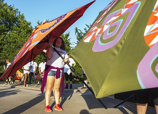 Maya Frazier, 15, of Lawrence, holds up a large patio umbrella as she shows it to the crowd gathered during Van Go's annual What Floats Your Boat fundraiser Saturday, June 20, 2015, at the Clinton Lake State Park marina.
