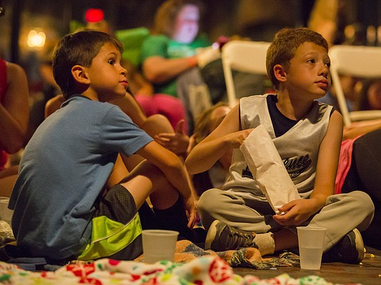 "Nine-year-old Santiago DeGarmo, right, and 8-year-old Jack Navarro, both of Lawrence, sit on the floor of Abe and Jakes, 8 E. Sixth St., as they watch a free screening of ""Back to the Future"" Thursday evening, June 25, 2015. The free movie, which was originally supposed to be shown at the Library Civic Plaza, 700 block of Vermont, was moved because of weather concerns. It was one of several movies to be shown as part of Dinner and a Movie."