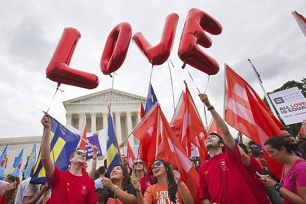 """Same-sex marriage supporters hold up balloons that spell the word """"love"""" as they wait outside of the Supreme Court in Washington, Friday, June 26, 2015, before the court declared that same-sex couples have a right to marry anywhere in the US."""