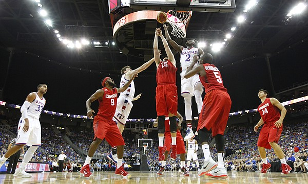 Kansas guard LaGerald Vick (2) and forward Hunter Mickelson (42) fight for a rebound in the paint with members of Team Canada during the third quarter of Friday's World University Games exhibition at Sprint Center.
