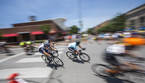 Cyclists competing in the men's pro race speed around a corner during the Tour of Lawrence downtown criterium Sunday, June 28, 2015.