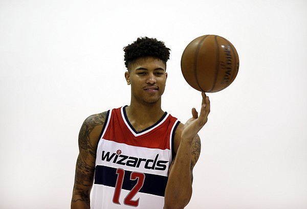 Washington Wizards' Kelly Oubre Jr. spins the ball on his finger during a portrait session for team photographer Stephen Gosling after an NBA basketball news conference, Friday, June 26, 2015, in Washington. Washington moved up four spots in the first round to get the Kansas freshman in a trade with the Atlanta Hawks, who selected Oubre with the 15th overall pick in the NBA draft the night before.. (AP Photo/Alex Brandon