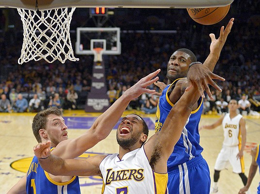 Los Angeles Lakers forward Xavier Henry, center, puts up a shot as Golden State Warriors center Ognjen Kuzmic, left, of Bosnia, and center Festus Ezeli, of Nigeria, defend during the second half of an NBA basketball game, Sunday, Nov. 16, 2014, in Los Angeles. The Warriors won 136-115. (AP Photo/Mark J. Terrill)