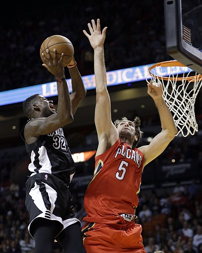 Miami Heat forward James Ennis (32) goes to the basket as New Orleans Pelicans center Jeff Withey (5) defends in the second half of an NBA basketball game in Miami, Saturday, Feb. 21, 2015. The Pelicans won 105-91. (AP Photo/Alan Diaz)