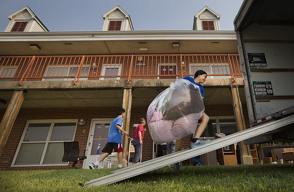 Hannah Au Yeong, 13, lugs a bag of blankets and pillows up a ramp into moving van at Stouffer Place apartments on Tuesday, June 30, 2015, the final day the family housing complex was open. The Au Yeong family, from Kuala Lumpur, Malaysia, lived at Stouffer Place for four years.