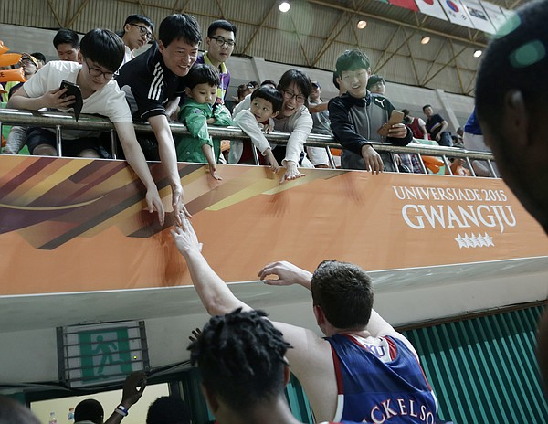 Kansas center Hunter Mickelson (42) reaches to touch fans while leaving the court after a Team USA 81-72 win over against Brazil Sunday, July 5, in Gwangju, South Korea.