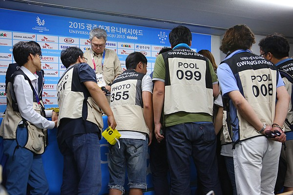 Photographers gather to get their photo vests and find out their shooting position in the stadium for the opening ceremony.