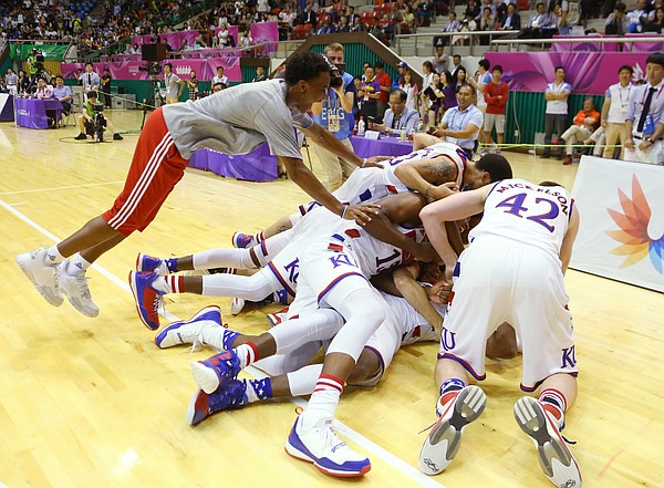 Devonte Graham, left, joins other Team USA players as they pile on Kansas guard Wayne Selden Jr. to celebrate their double-overtime win against Germany Monday, July 13, at the World University Games in South Korea.