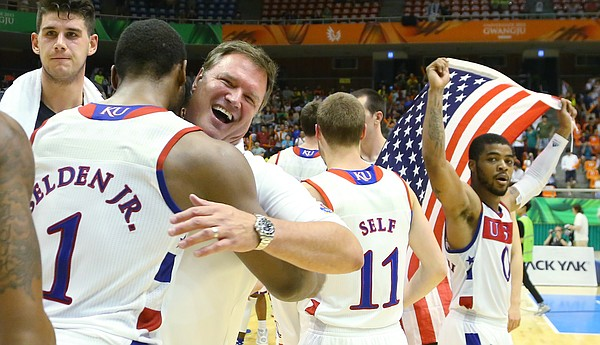 Team USA coach Bill Self, center, hugs Kansas guard Wayne Selden Jr. (1) as Frank Mason III carries an American flag after a Team USA double-overtime win against Germany Monday, July 13, at the World University Games in South Korea.