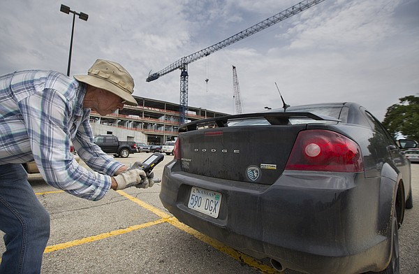 Kansas University parking control officer Steve DeVillier photographs a license plate as he works to print out a citation for an illegally parked vehicle in the lot south of Robinson Gymnasium on Wednesday, July 15, 2015. Starting with the fall 2015 semester, KU Parking will use e-permits, and eventually move from printed tickets to e-mailed ones.
