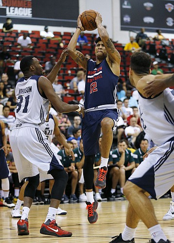 Washington Wizards' Kelly Oubre Jr. shots over Utah Jazz's JaJuan Johnson during the first half of an NBA summer league basketball game Wednesday, July 15, 2015, in Las Vegas. (AP Photo/John Locher)
