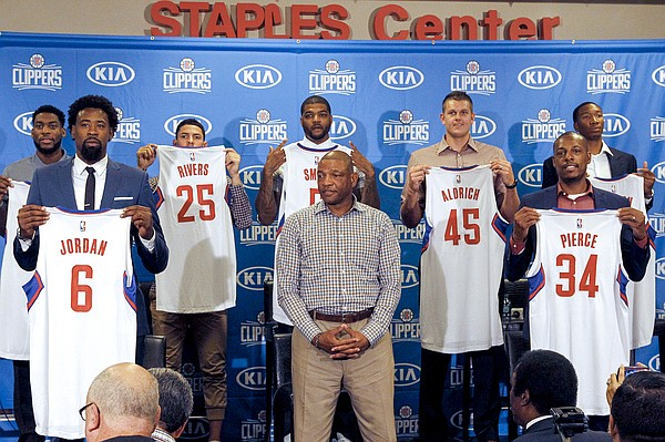 Los Angeles Clipper, head coach Doc Rivers, center, poses team players, from left, Branden Dawson, 22, DeAndre Jordan, 6, Austin Rivers, 25, Josh Smith, 5, Cole Aldrich, 45, Paul Pierce, 34, and Wesley Johnson, 33, far right, at at a news conference in Los Angeles on Tuesday, July 21, 2015. The Clippers managed to keep DeAndre Jordan after he changed his mind about his verbal commitment to Dallas Mavericks. They offered everything he wanted, including a fresh start and a bigger offensive role. When Jordan thought about it a little more, the craziest free-agent recruitment story in recent NBA history ended with him back on the Los Angeles Clippers. (AP Photo/Nick Ut)