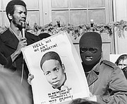 "Ron Washington, chairman of the Black Students Union at Kansas University, left, addresses a strike rally on campus in this file photo from December 1970, as an unidentified youth displays a sign in memory of Rick ""Tiger"" Dowdell. Dowdell was fatally shot while fleeing police on July 16, 1970."