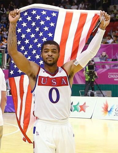 Kansas guard Frank Mason III (0) carries the United States flag after a Team USA double-overtime victory against Germany, Monday, July 13, 2015, at the World University Games in South Korea.