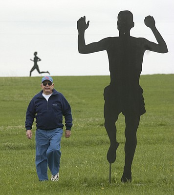 Bob Timmons, the former Kansas University track coach who created the Rim Rock Farm in Jefferson County, walks near silhouettes of Jim Ryun and Billy Mills, both former KU standouts, in this file photo from 2005.
