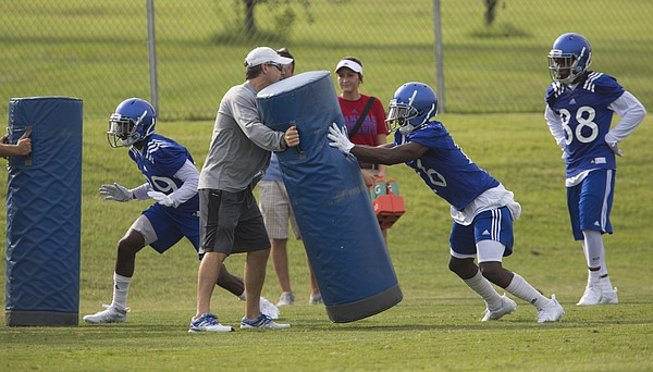 Kansas offensive coordinator Rob Likens holds a pad upright as receivers DeAnte Ford, left, and Steven Sims Jr. practice coming off a block during the first day of practice on Thursday, Aug. 6, 2015 at the fields south of Anschutz Pavilion.