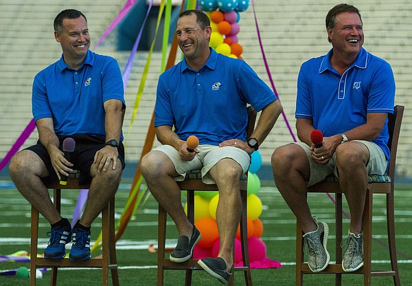 Kansas women's basketball coach Brandon Schneider, football coach David Beaty and men's basketball coach Bill Self speak at KU Traditions Night Saturday evening at Memorial Stadium. The annual event held before the start of each new school year aims to teach incoming freshmen about the traditions that make KU unique. The three coaches all agreed that their favorite tradition was the Rock Chalk Chant at the end of games, signaling to the other team that the game was over.