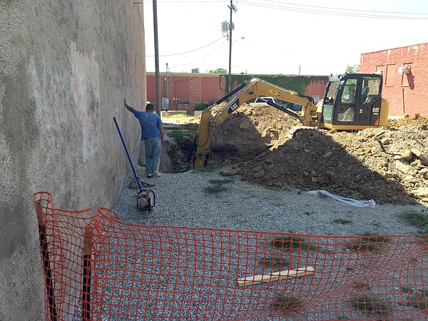 A backhoe digs small holes in the vacant lot between 715 Restaurant and The Eldridge Hotel, Monday, Aug. 24, 2015.