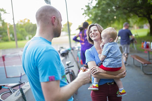 Husband and wife Spencer and Ali Sward laugh during a break in action during a bike polo game on Thursday, Aug. 13, 2015 at Edgewood Park in East Lawrence. Also pictured with them is their son, Desmond, 18 months. The couple say they met playing bike polo.