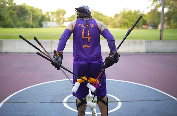 Malakai Edison shuffles the mallets before tossing three on either side of the court to determine the teams during a bike polo game on Thursday, Aug. 13, 2015 at Edgewood Park in East Lawrence.