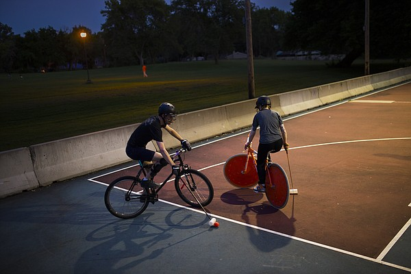 Opposing players Peter Lewis, a Scary Larry founder, looks to make a move to get around Kira Monet during a bike polo game on Thursday, Aug. 13, 2015 at Edgewood Park in East Lawrence.