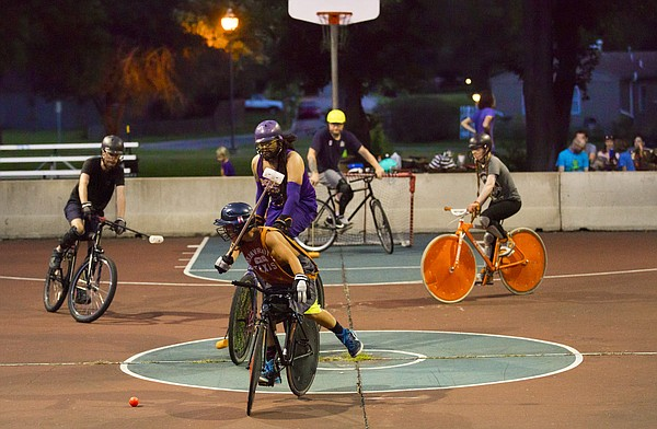 Twelve-year-old Tyler Crain raises his mallet to take a shot during a bike polo game on Thursday, Aug. 13, 2015 at Edgewood Park in East Lawrence. Crain is among the youngest of the regular bike polo competitors.