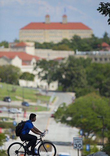 A student bikes across the intersection at Engel Road and 15th Street en route to Daisy Hill, Wednesday, Sept. 9, 2015, on the campus of Kansas University. In the newly-released U.S. News and World Report's Best Colleges list, KU is ranked 115th among national universities.