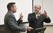 Kansas University professor of law Mark Johnson, right,  and Kansas Secretary of State Kris Kobach argue opposing opinions about the necessity of Voter ID laws during a debate Thursday, Sept. 10, 2015 in Green Hall on the campus of Kansas University.
