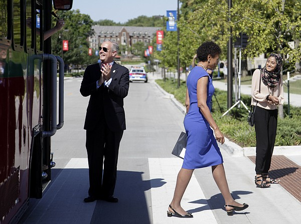 Tim Caboni, vice chancellor for public affairs at KU, left, greets passengers exiting a motorized trolley car in front of Strong Hall Friday, Sept. 11, 2015. At right is KU Chancellor Bernadette Gray-Little. KU held a formal dedication ceremony for Jayhawk Boulevard, which is undergoing a four-year reconstruction project that includes rebuilding the roadway and replanting the historic tree canopy over it.