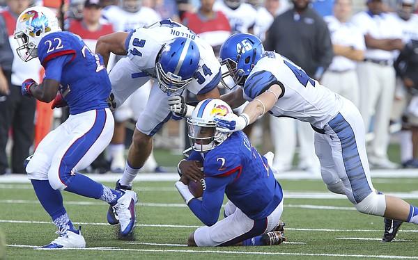 Kansas quarterback Montell Cozart (2) ducks under Memphis tacklers Memphis linebacker Jackson Dillon (34) and linebacker Noah Robinson (45) during the quarter on Saturday, Sept. 12, 2015 at Memorial Stadium. At left is Kansas running back Ke'aun Kinner (22).
