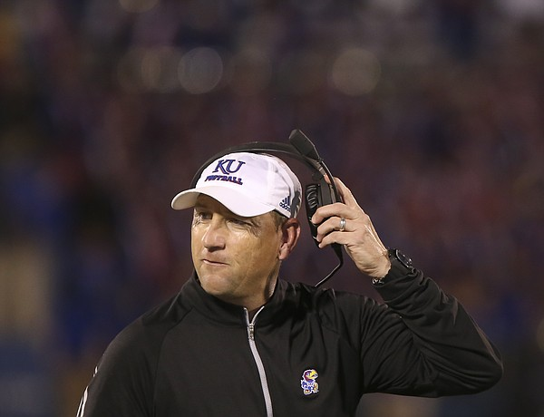 Kansas head coach David Beaty pulls off his headset after an offensive series during the fourth quarter on Saturday, Sept. 12, 2015 at Memorial Stadium.