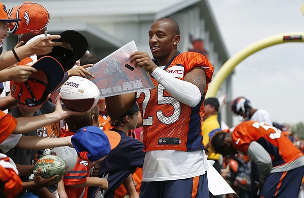 Denver Broncos cornerback Chris Harris signs autographs after drills at the team's NFL football training camp Friday, Aug. 7, 2015, in Englewood, Colo. (AP Photo/David Zalubowski)